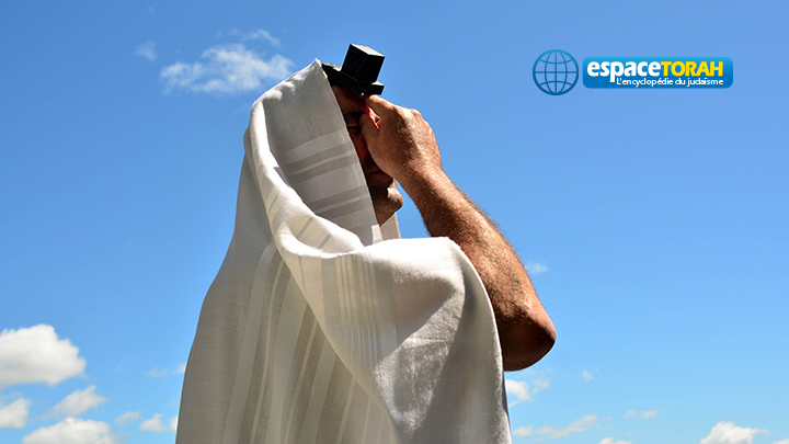 A Jewish man wearing Tallit and Tefillin read from the Torah book pray to God under a blue sky with sheep clouds. Photo by Rafael Ben-Ari/Chameleons Eye